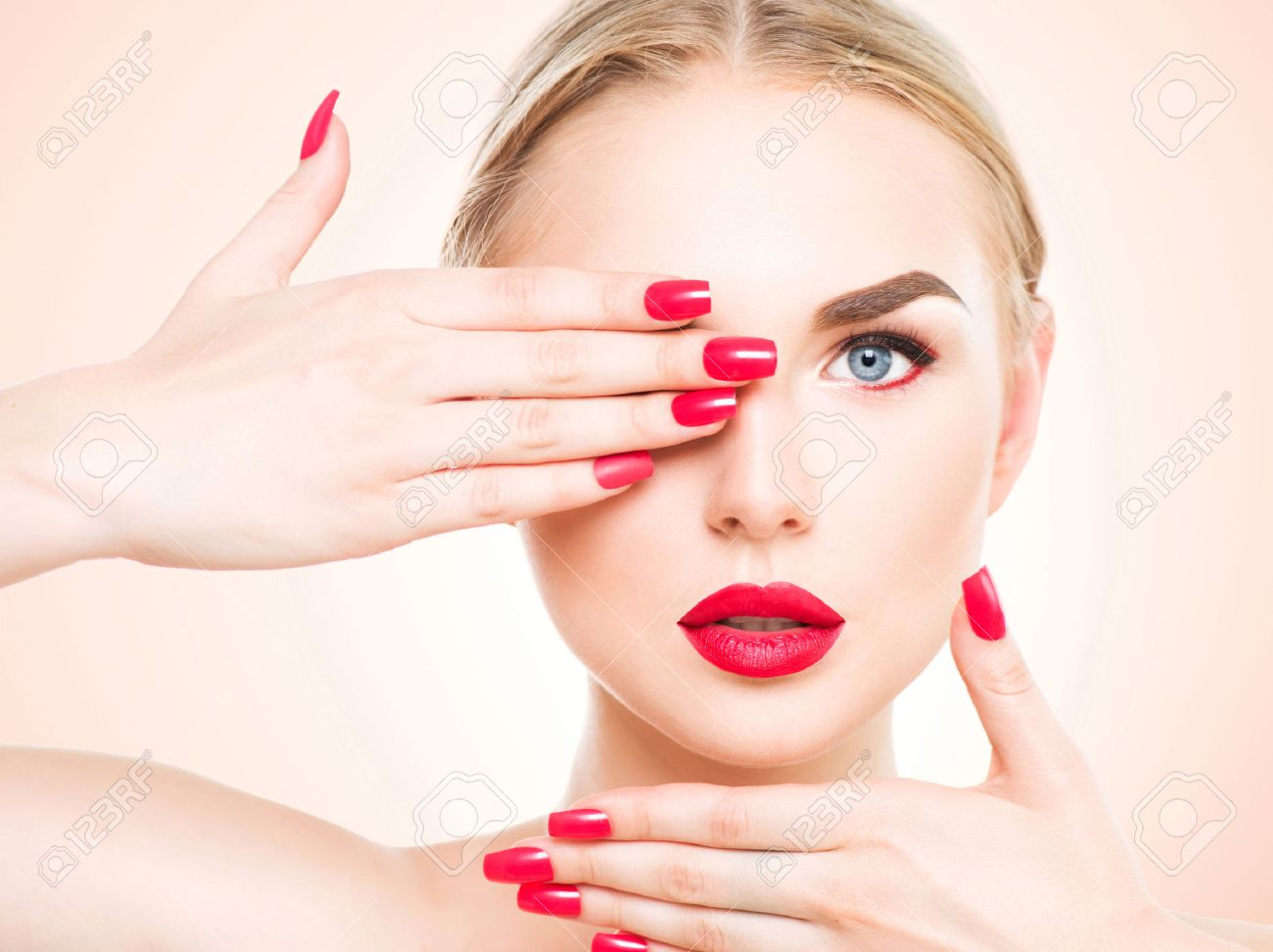 Beautiful woman with blond hair. Fashion model with red lipstick and red nails. Portrait
