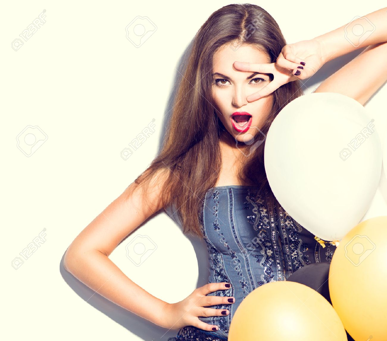 Beautiful fashion model girl with colorful balloons posing over white Stock Photo - 45198210