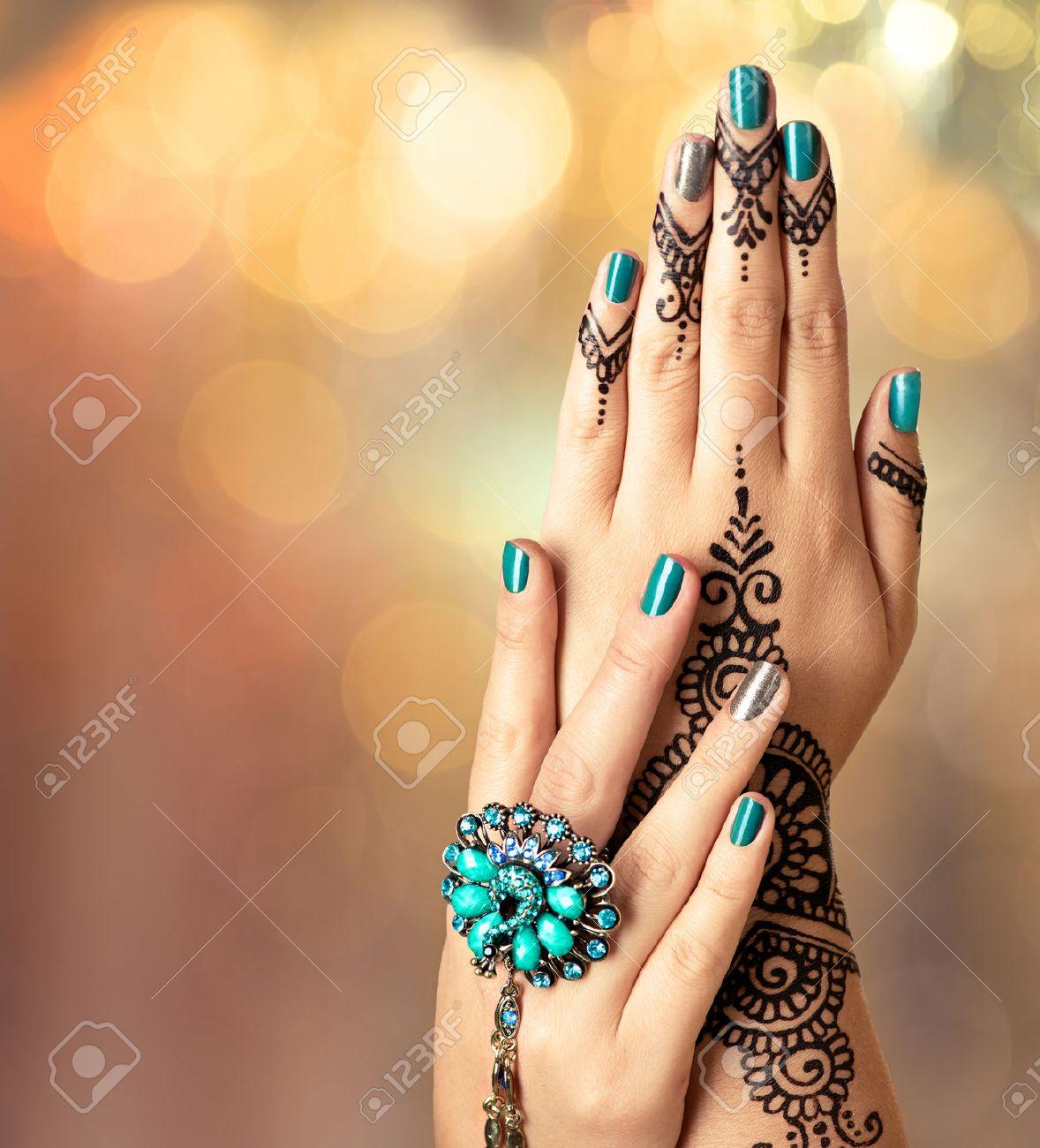 Tatouage Oreille Femme dedans mehndi tatouage. mains de femme avec tatouage au henné noir banque d