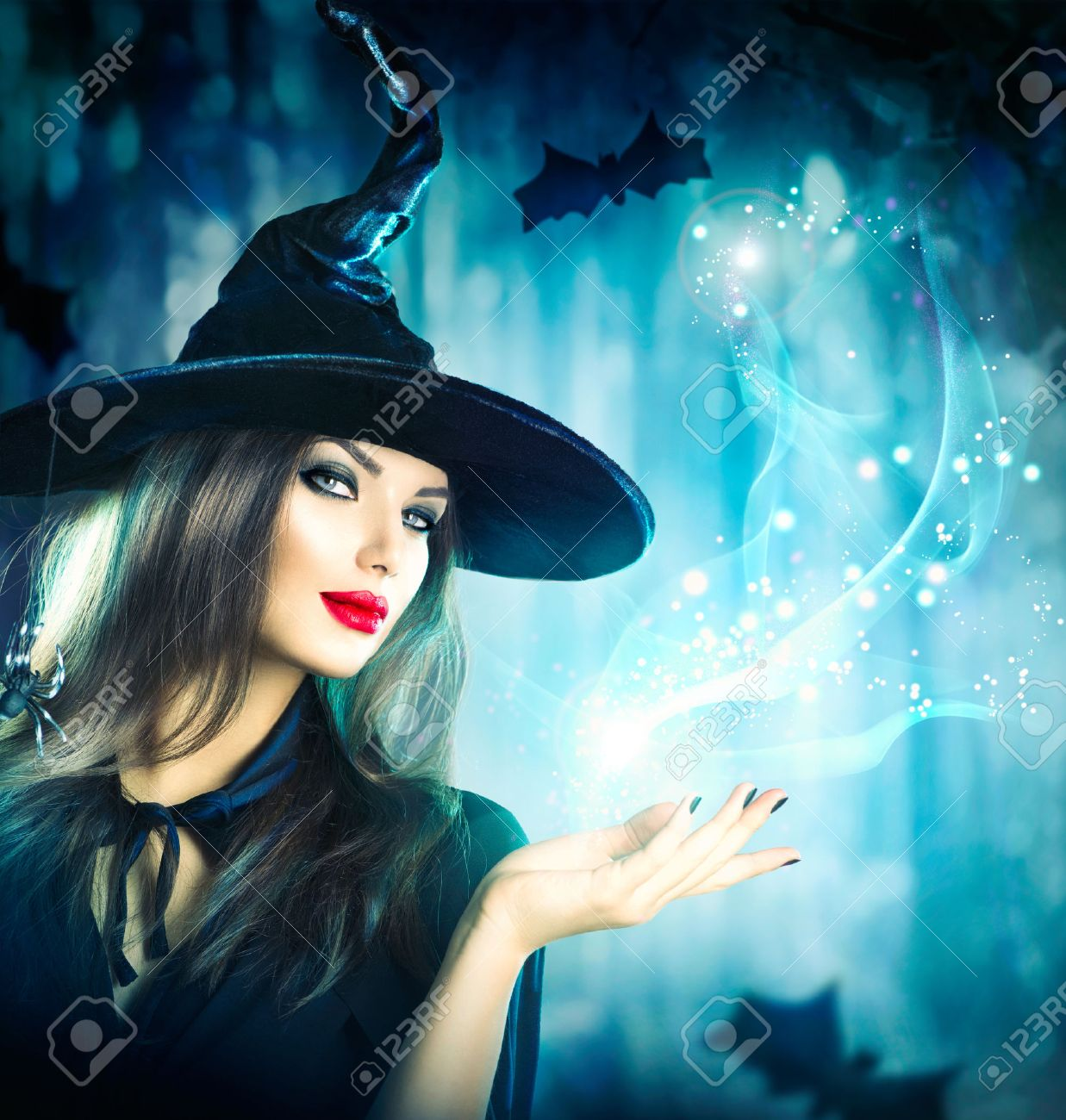 Halloween Witch holding magical light in her hand - 46883611