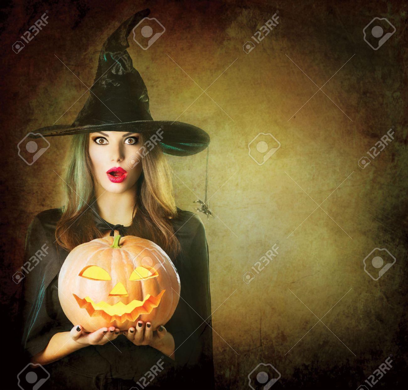 Halloween Witch holding carved Jack lantern pumpkin - 46883619