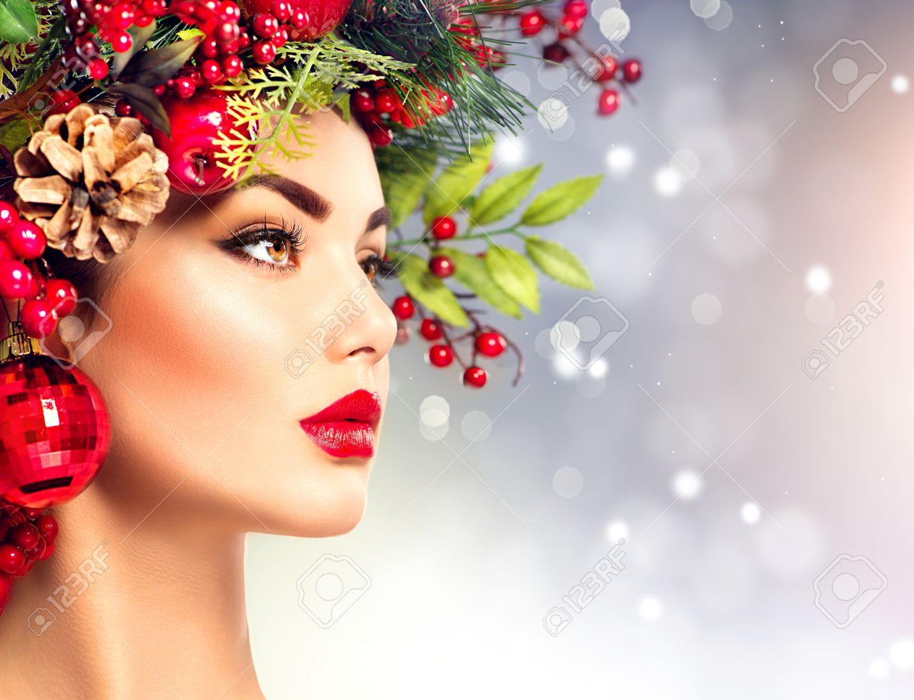 Foto de archivo , Mujer modelo de moda de Navidad. El peinado y el maquillaje de vacaciones