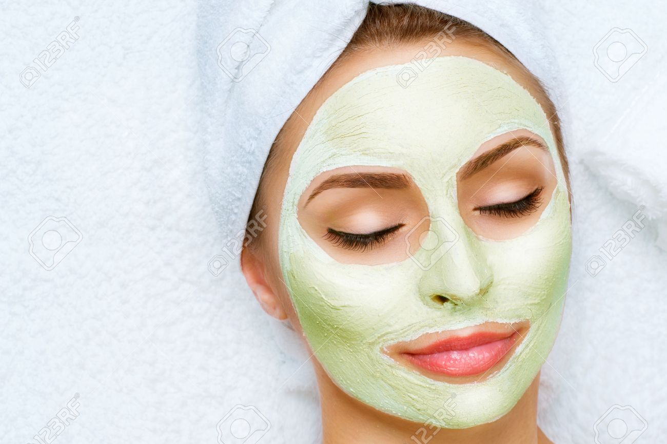 Portrait of beautiful girl with a towel on her head applying facial mask - 51140724