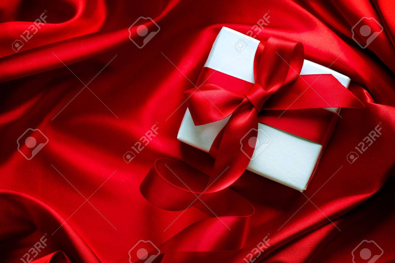 Valentine gift box with red satin ribbon on red silk background - 51849723