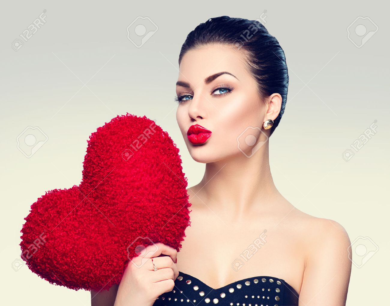 Gorgeous young brunette woman with heart shaped red pillow Stock Photo - 51892359