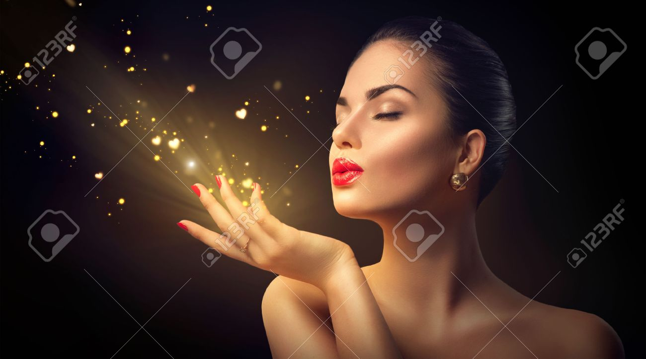 Beauty young woman blowing magic dust with golden hearts Stock Photo - 51755918