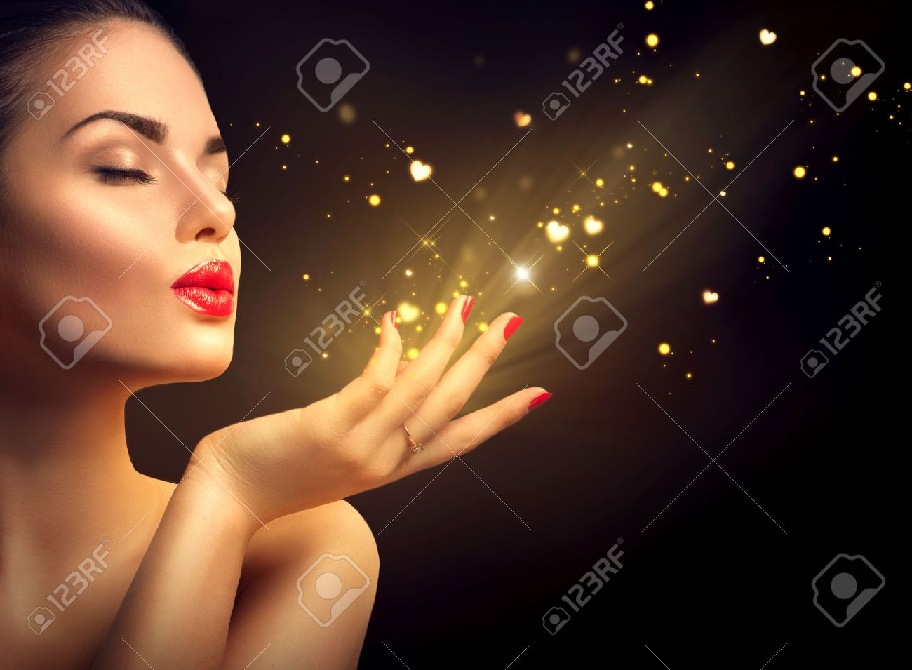 Beauty young woman blowing magic dust with golden hearts - 51755923