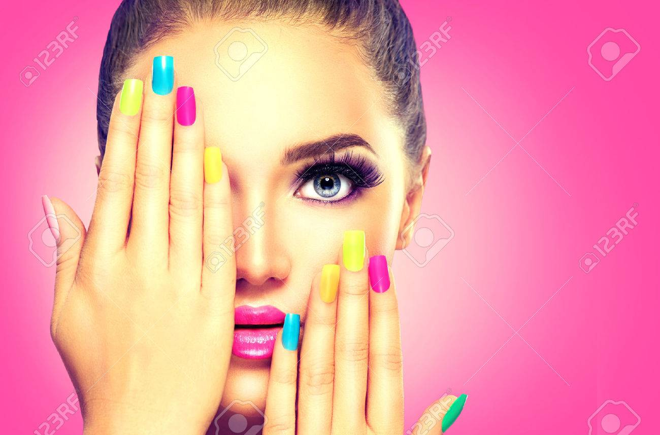 Beauty girl face with colorful nail polish - 54596695