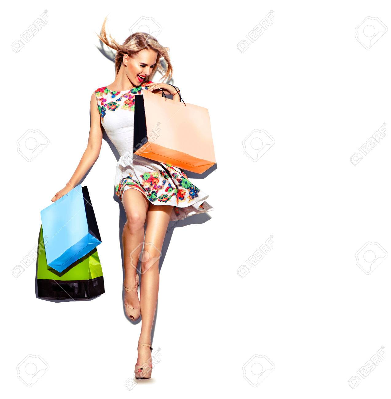Beauty woman with shopping bags in short white dress. Shopping - 55256203