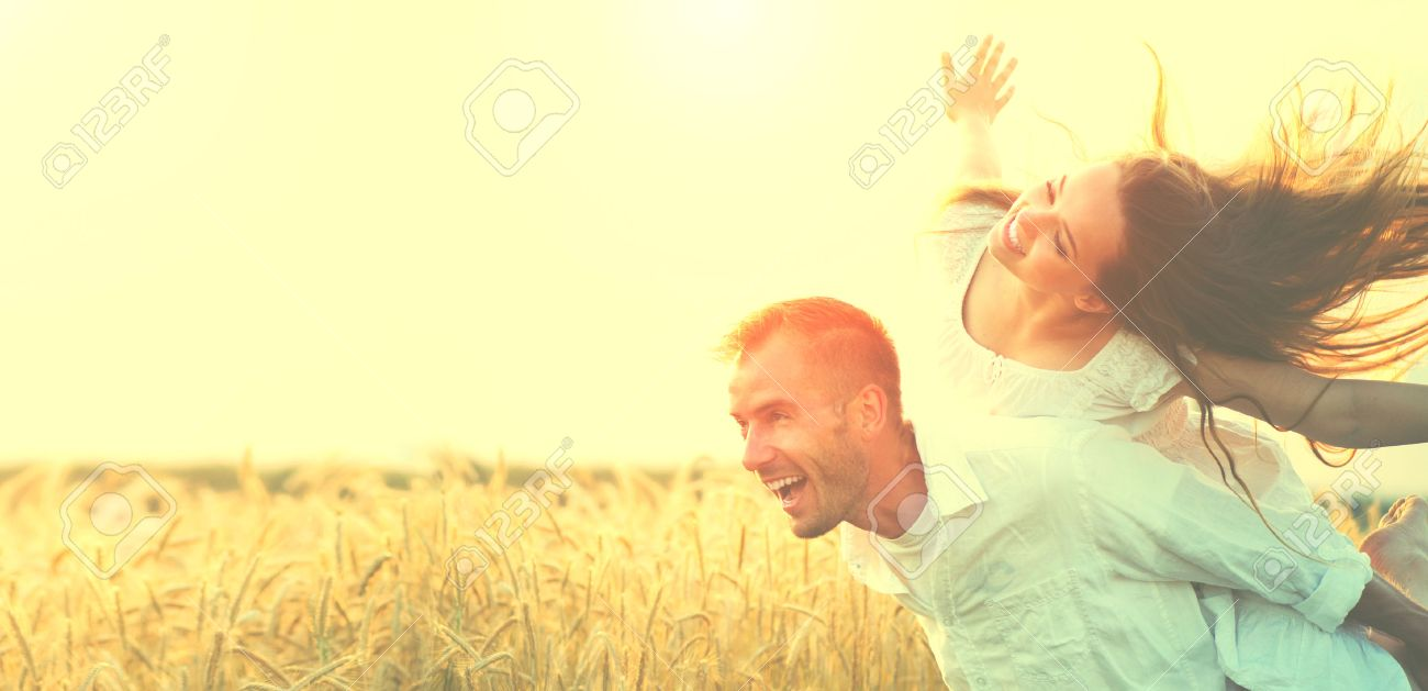 Happy couple having fun outdoors on wheat field over sunset - 60029263