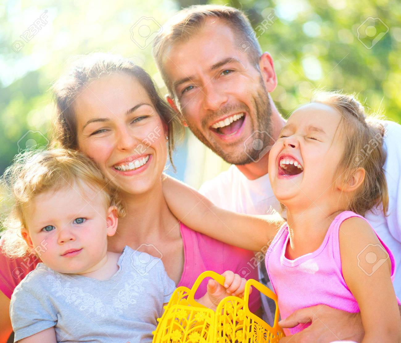 Happy joyful young family with little children outdoors - 62172123