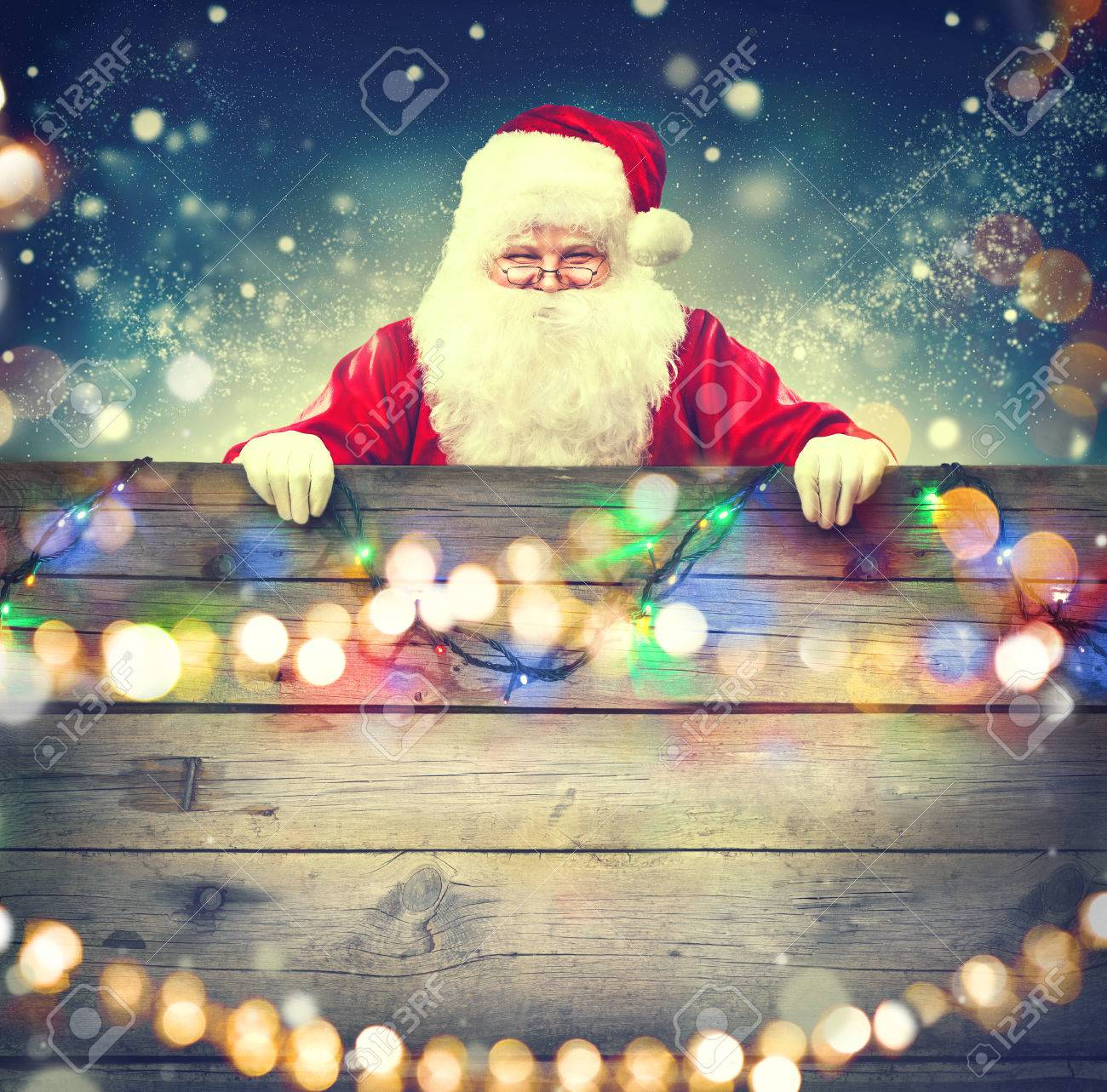 happy santa claus holding wooden banner background. christmas