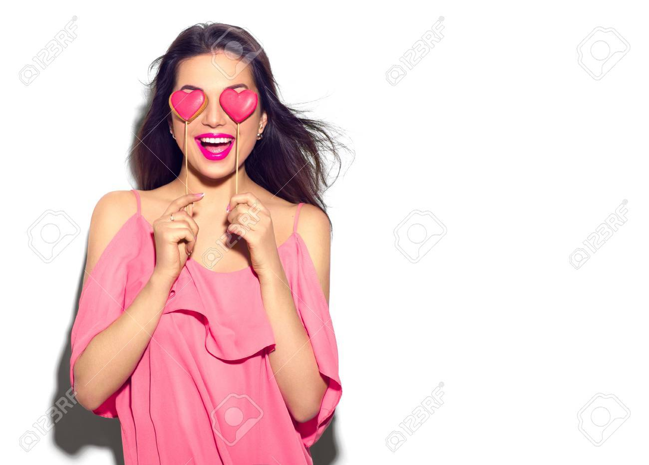 Valentines Day. Beauty joyful young fashion model girl with Valentine Heart shaped cookies in her hands Banque d'images - 69431335