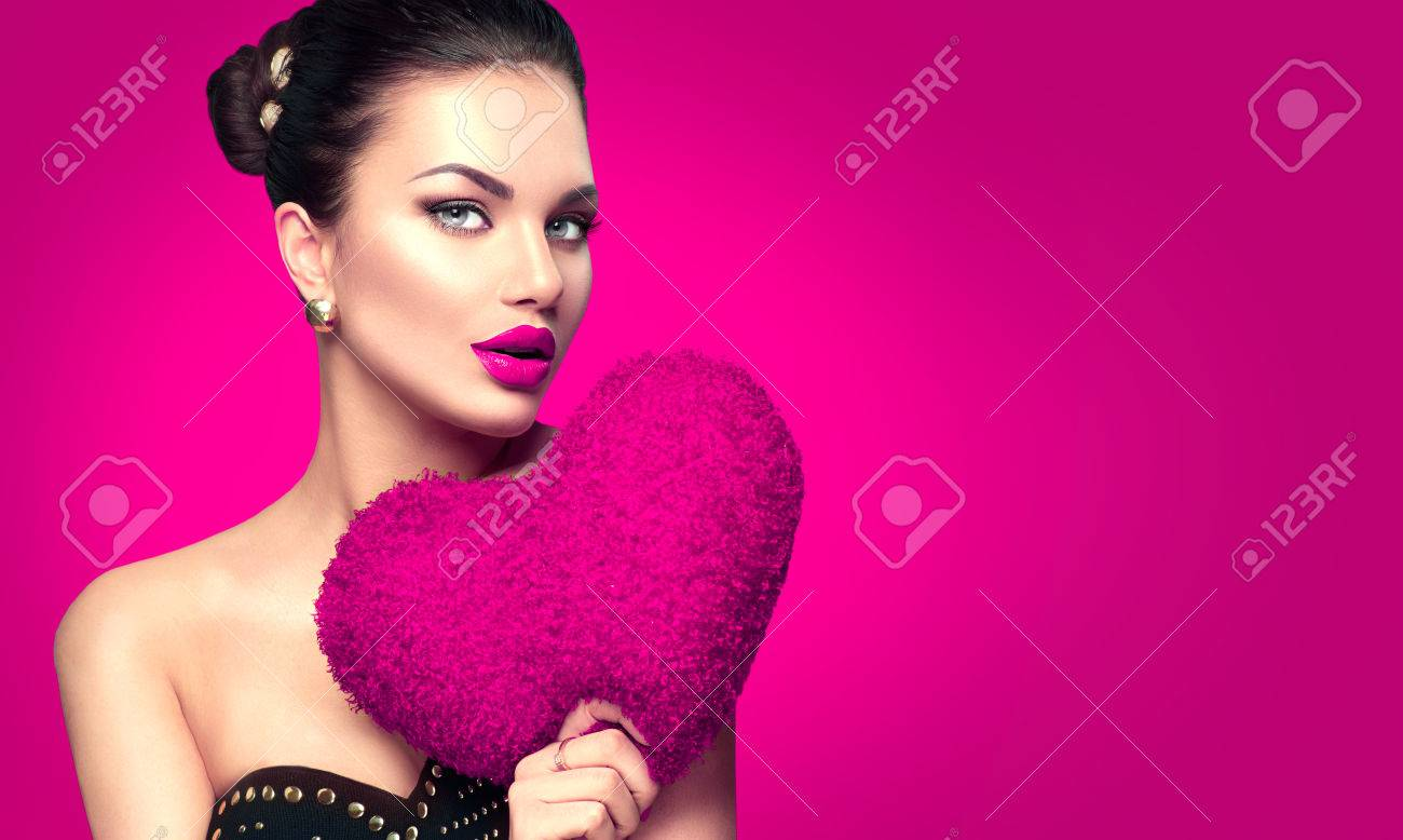 Sexy Valentine model girl portrait. Gorgeous Valentines young brunette woman with heart shaped purple pillow on pink background Banque d'images - 69431396