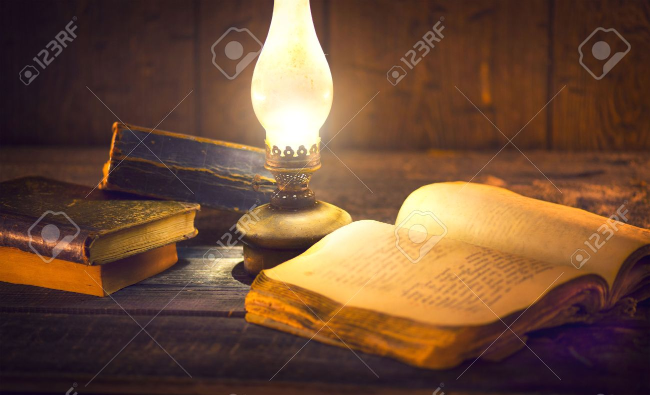 Old books and vintage oil lamp. Kerosene lantern and open old book on wooden table Banque d'images - 70349021