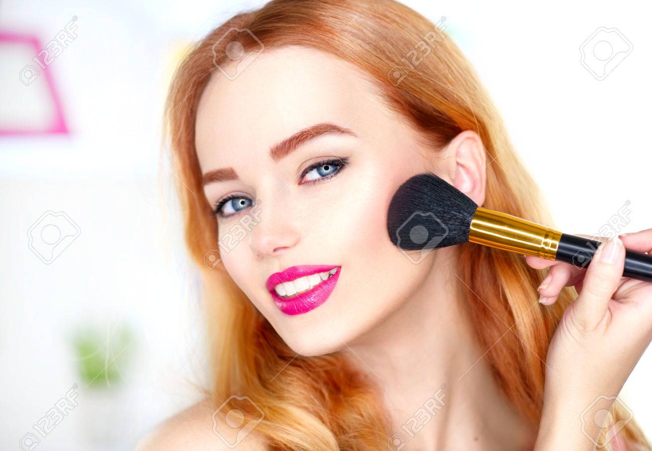 Beauty woman applying makeup. Beautiful girl looking in the mirror and applying cosmetic with a big brush - 75720341