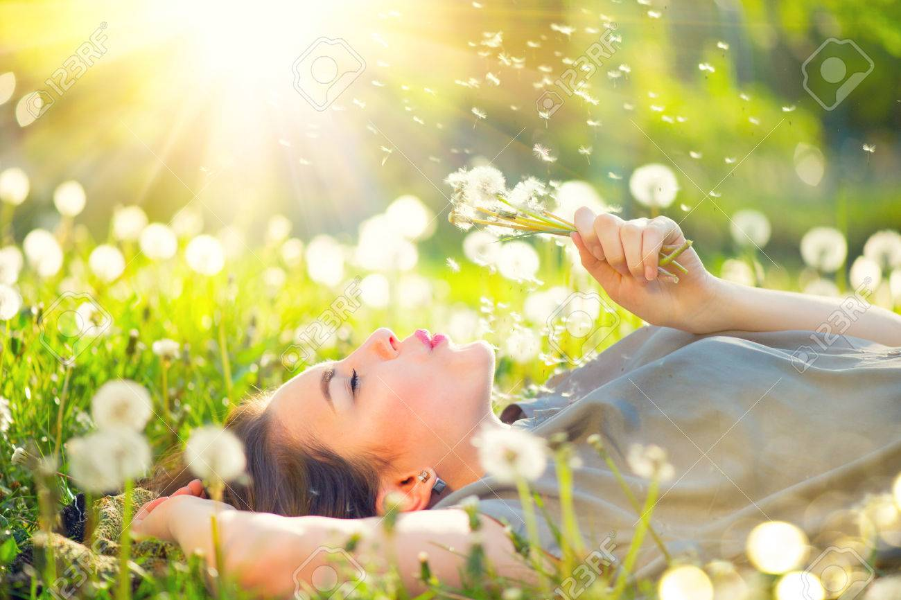 Beautiful young woman lying on the field in green grass and blowing dandelion Banque d'images - 78264157