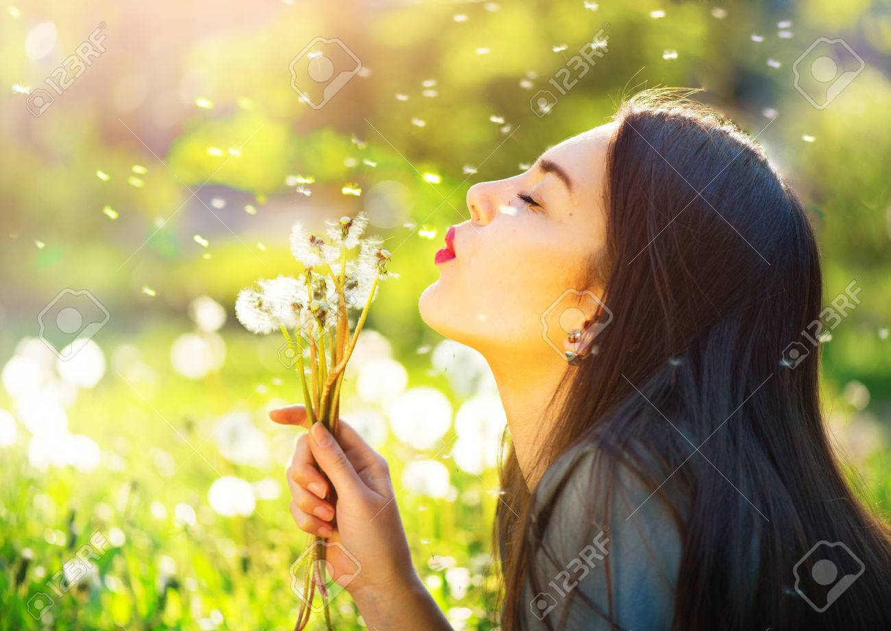 Beautiful young woman blowing dandelions and smiling - 80238029