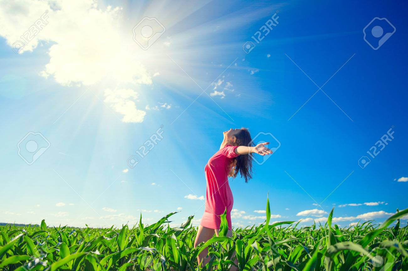 Beauty girl on summer field rising hands over blue clear sky. Happy young healthy woman enjoying nature outdoors Banque d'images - 81849104