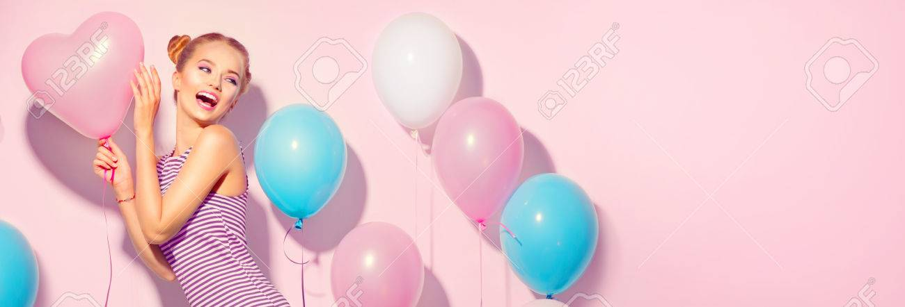Beauty joyful teenage girl with colorful air balloons having fun over pink background - 84326555