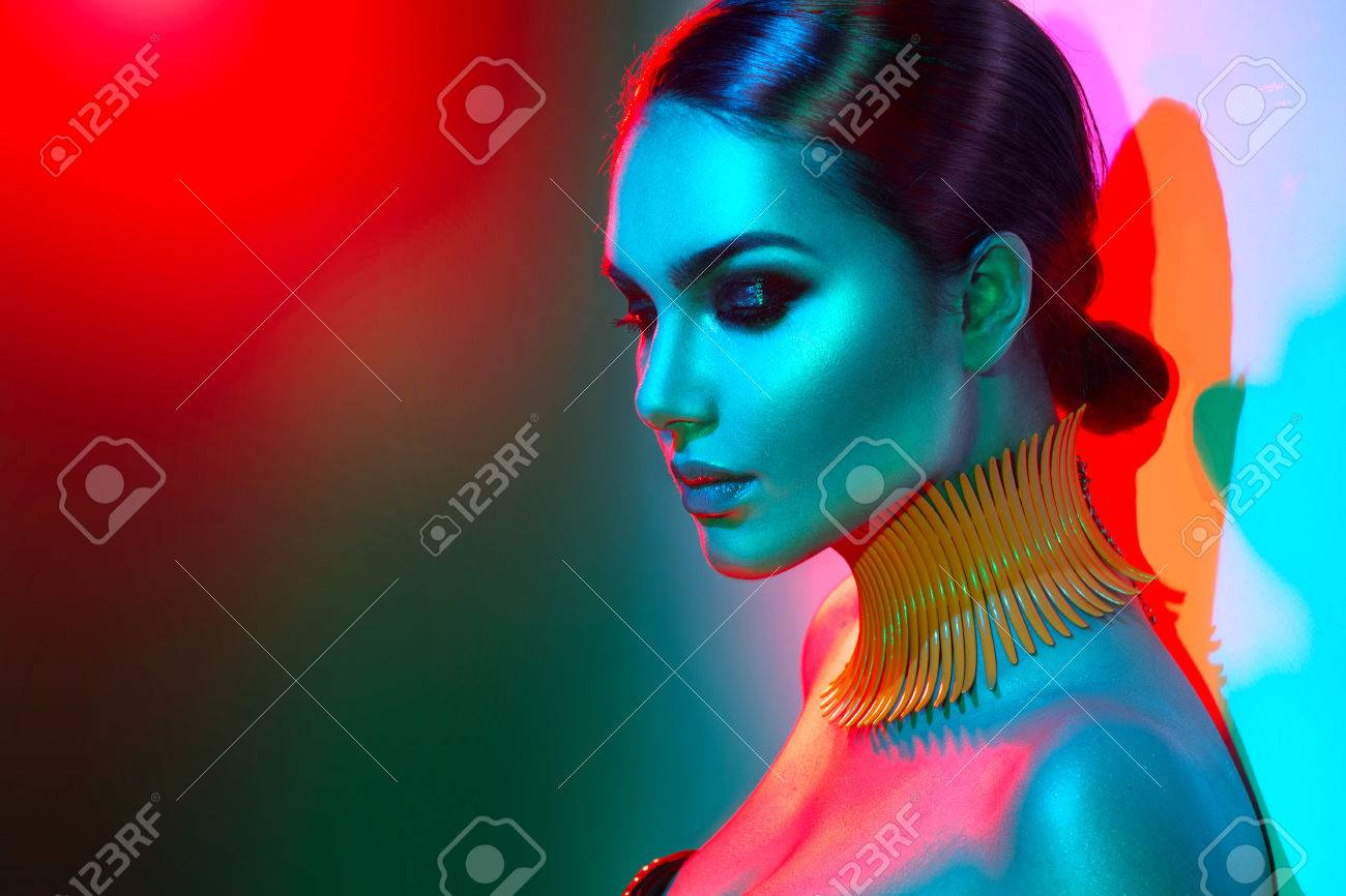 Fashion model woman in colorful bright lights posing. Portrait of beautiful sexy girl with trendy makeup Banque d'images - 84778572