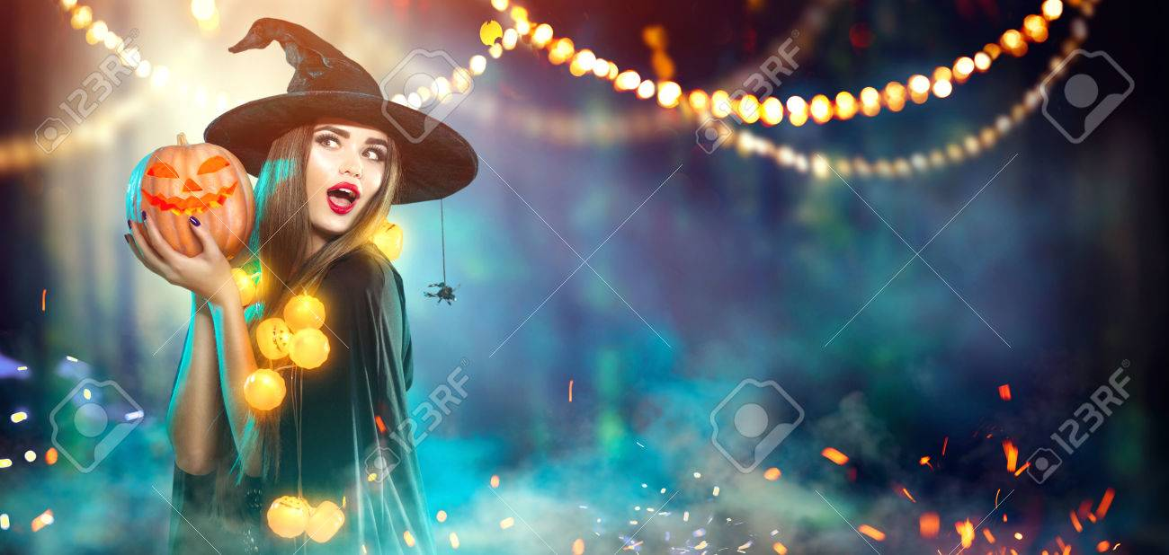Halloween. Witch with a carved pumpkin and magic lights in a dark forest - 86272565