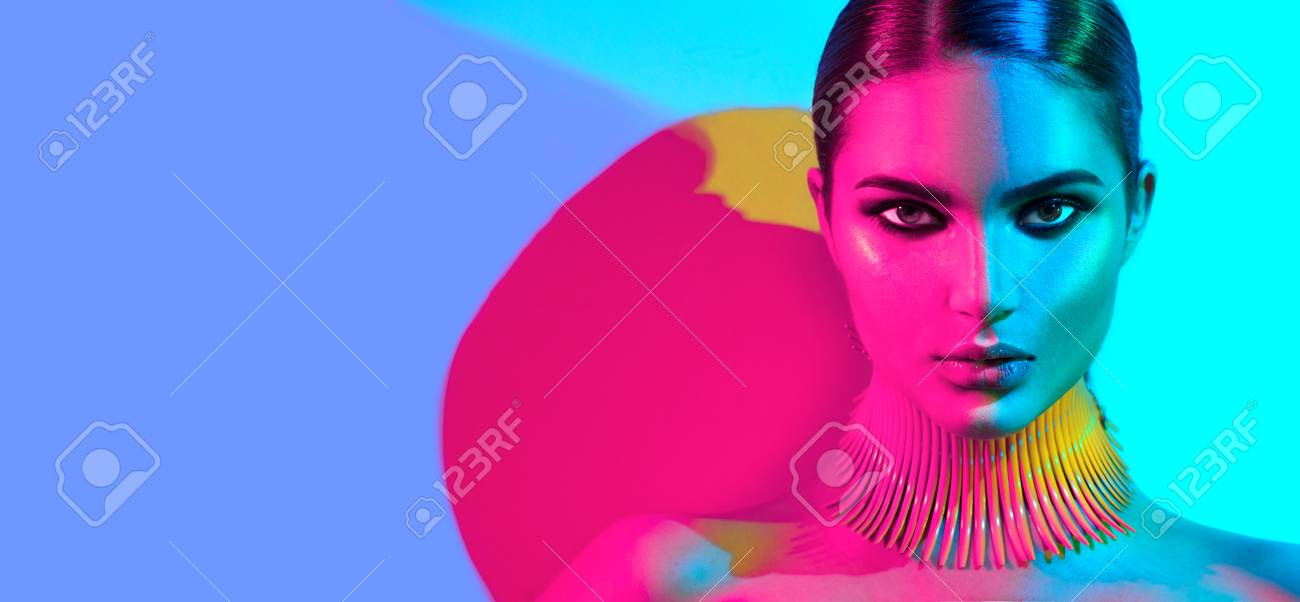 Fashion model woman in colorful bright lights posing. Portrait of beautiful girl with trendy makeup - 88170751