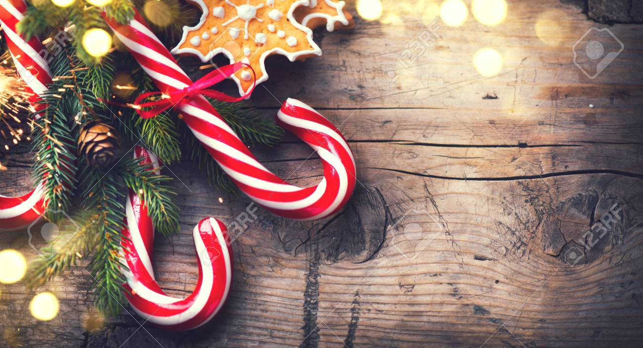 Christmas holiday background with gingerbread cookies, candy cane and evergreens border over wooden table - 90598928
