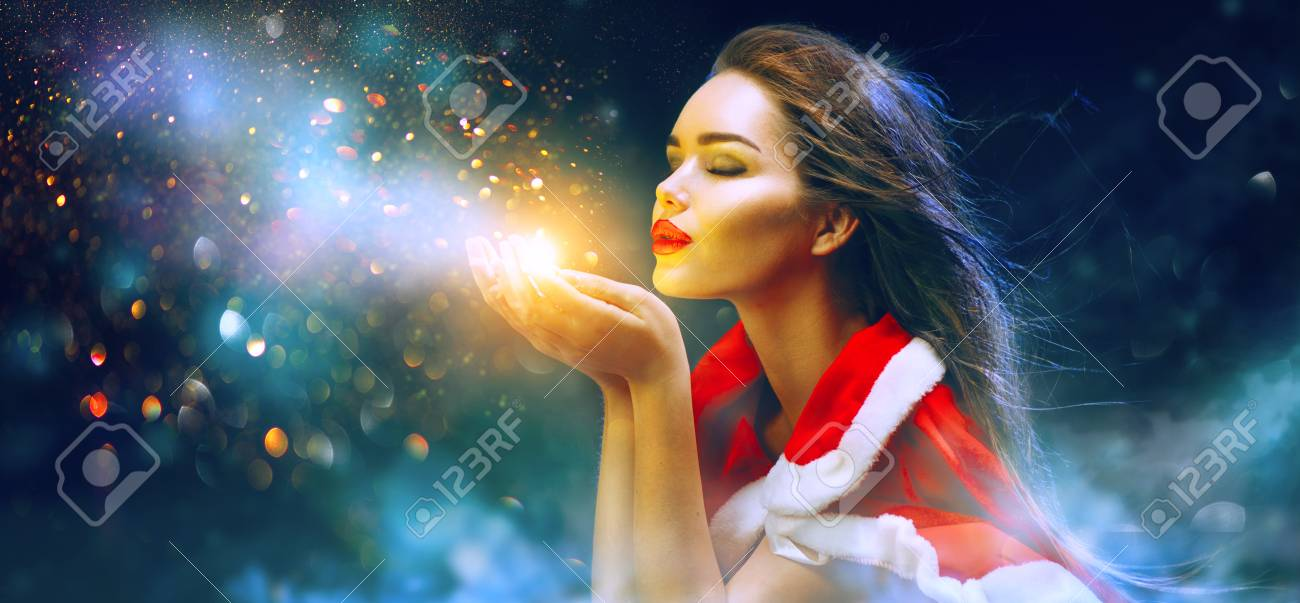 Christmas scene. Sexy Santa. Brunette young woman in party costume blowing snow over holiday blurred background - 92324801