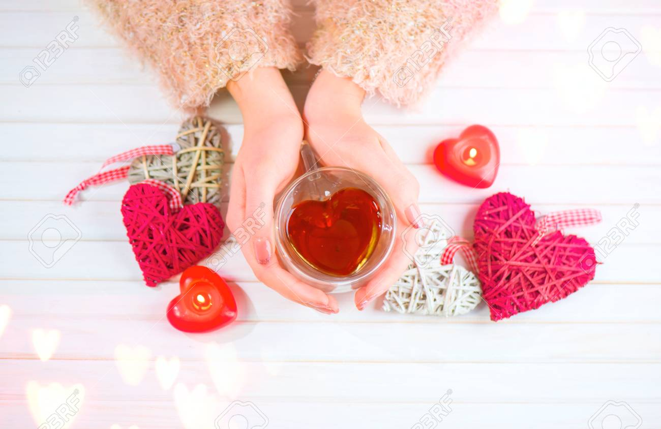St. Valentine's Day. Young woman hands holding heart shaped tea cup over wooden background. Love concept. Top view - 94662298