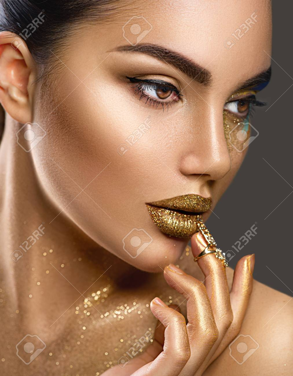 Fashion art makeup. Portrait of beauty woman with golden skin. Glamour shiny professional makeup - 95802170