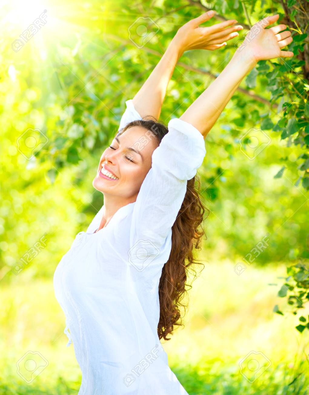 Beautiful young woman enjoying nature outdoor. Happy and smiling brunette girl with healthy smile relaxing in the summer park - 96826047