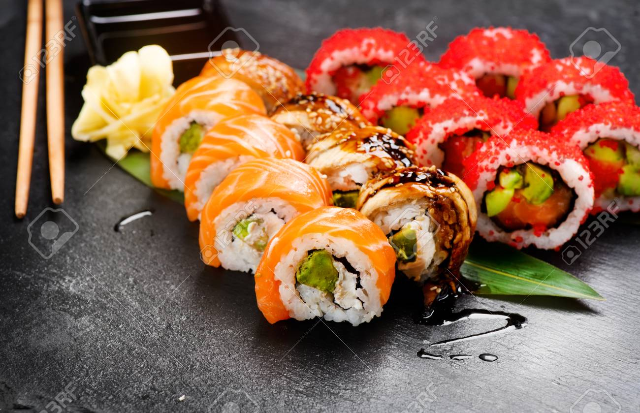 Sushi rolls closeup. Japanese food in restaurant. Roll with salmon, eel, vegetables and flying fish caviar on black slate background - 99967504