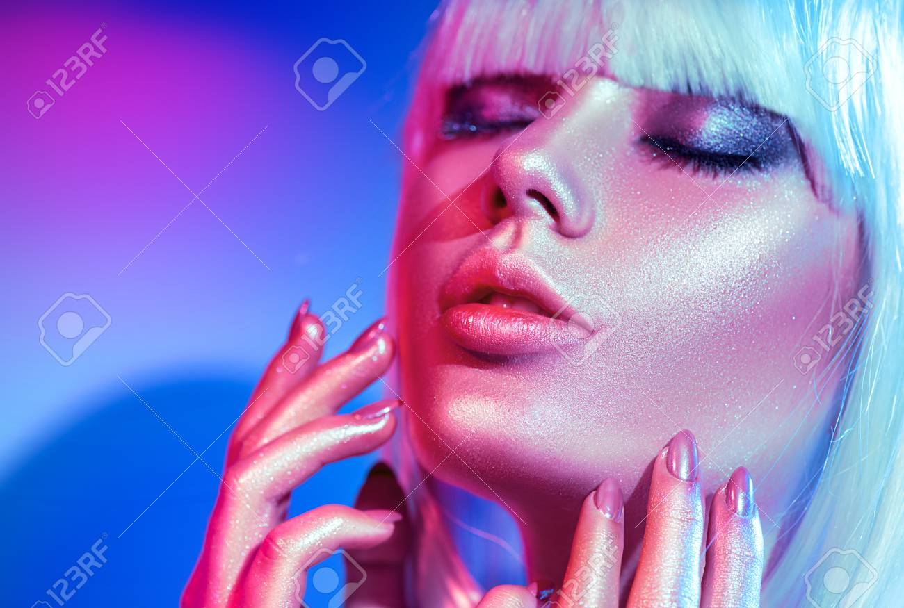 Fashion model woman in colorful bright sparkles and neon lights posing in studio, portrait of beautiful girl, trendy glowing make-up - 103269058