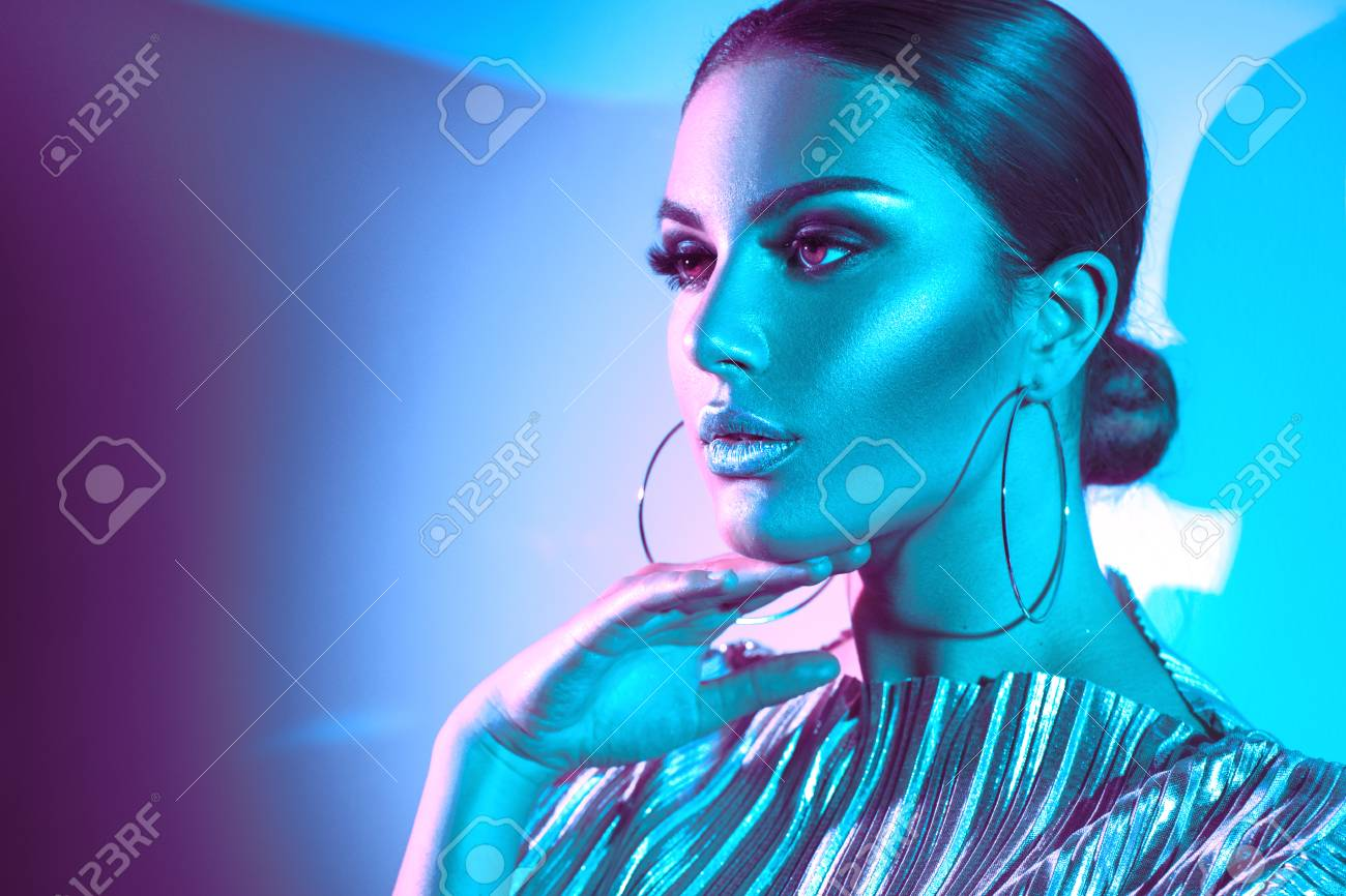 Fashion model brunette woman in colorful bright neon lights posing in studio. Beautiful girl, trendy glowing makeup, metallic silver lips - 104315276