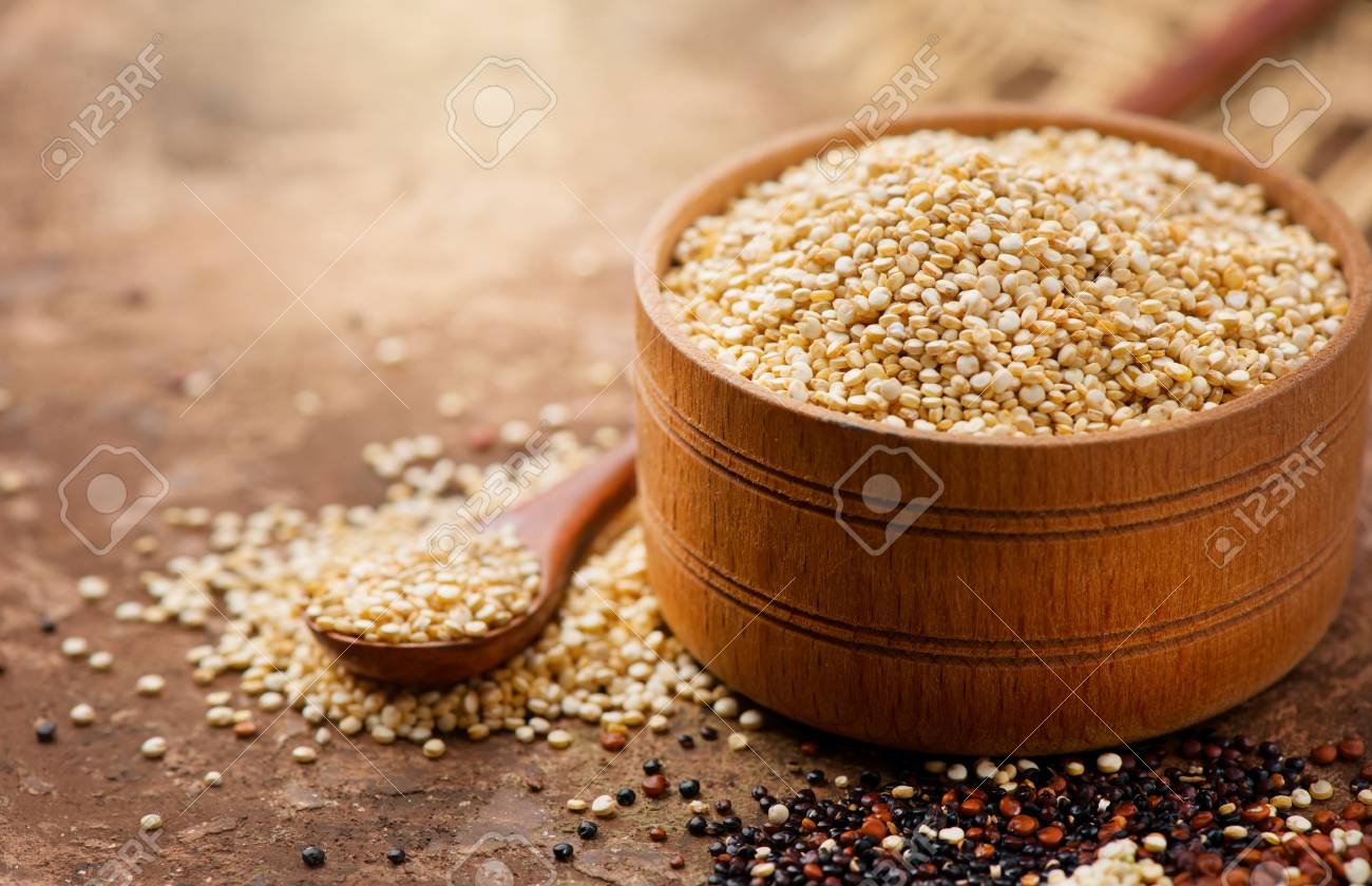 Quinoa. White quinoa grains in a wooden bowl. Healthy food. Dieting concept. Seeds of white, red and black quinoa - Chenopodium quinoa - 109561172