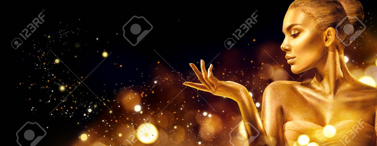 Gold Christmas woman. Beauty fashion model girl with golden makeup, hair and jewellery pointing hand on black background - 112144548
