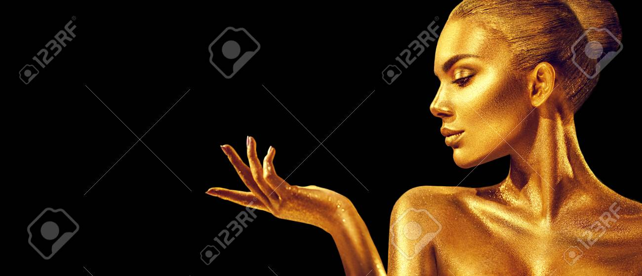 Golden woman. Beauty fashion model girl with golden skin, makeup, hair and jewellery on black background. Fashion art portrait - 112144826