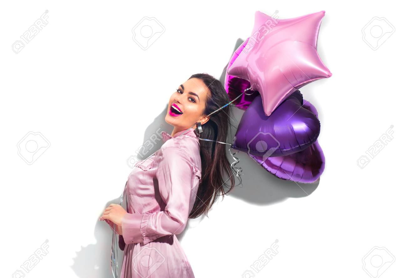Beauty fashion model party girl with heart shaped air balloons having fun. Birthday party, Valentines Day. Beautiful young brunette woman over white background - 114389754