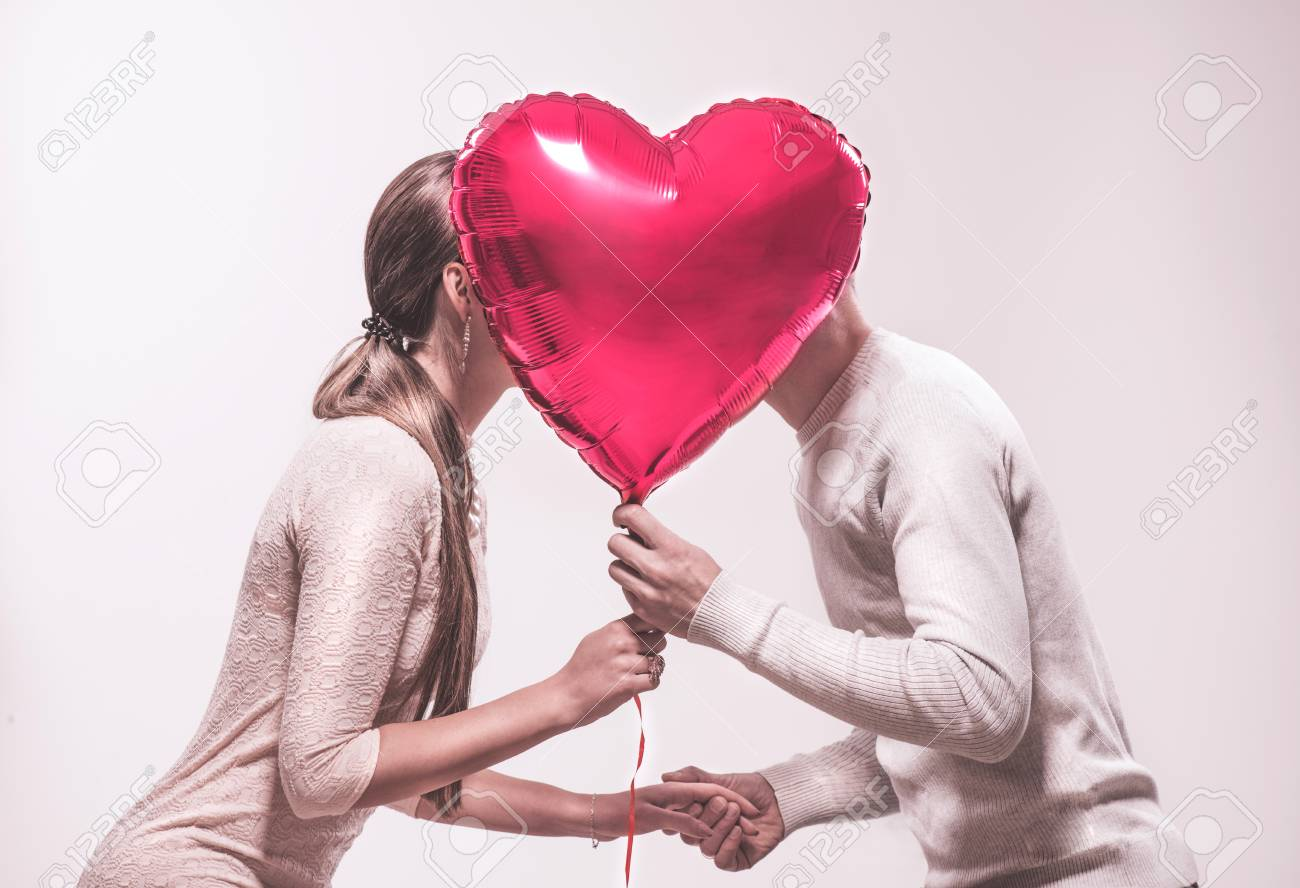 Valentine's day. Happy joyful couple holding heart shaped air balloon and kissing. Love. Happy Valentine's Day celebrating - 117555538