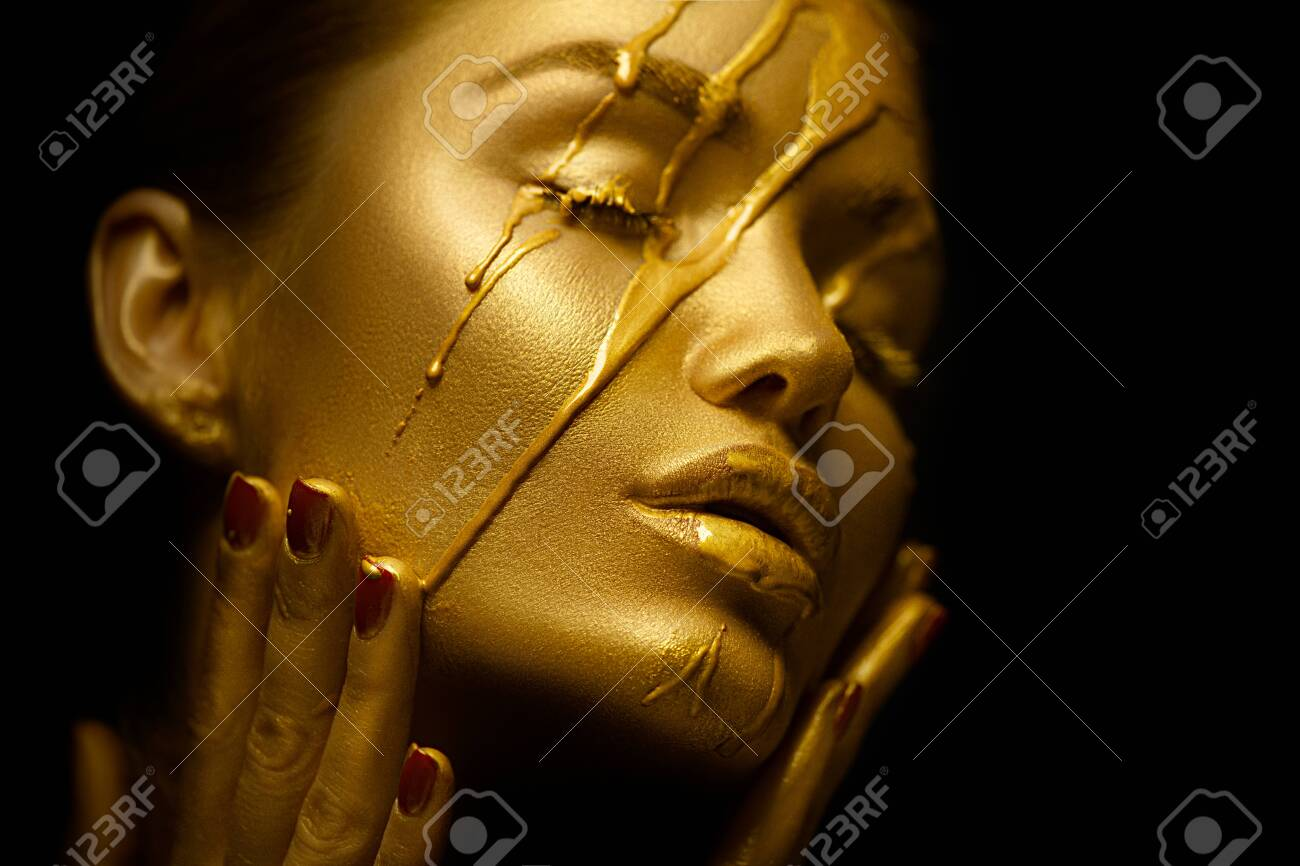 Sexy beauty woman with golden metallic skin. Gold paint smudges drips from the face and lips. Creative makeup - 126362870