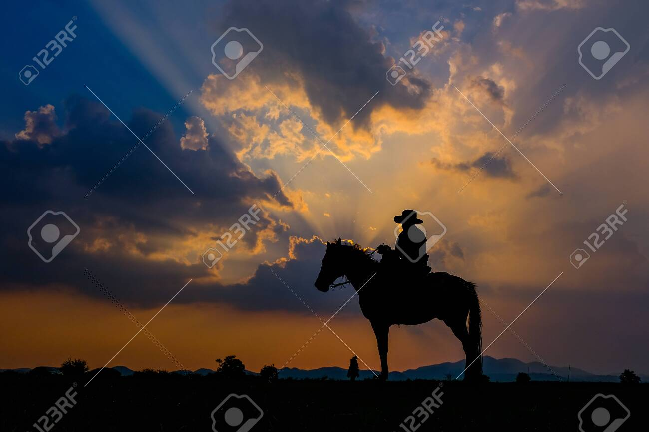 A man in a cowboy outfit with his horse - 123812306