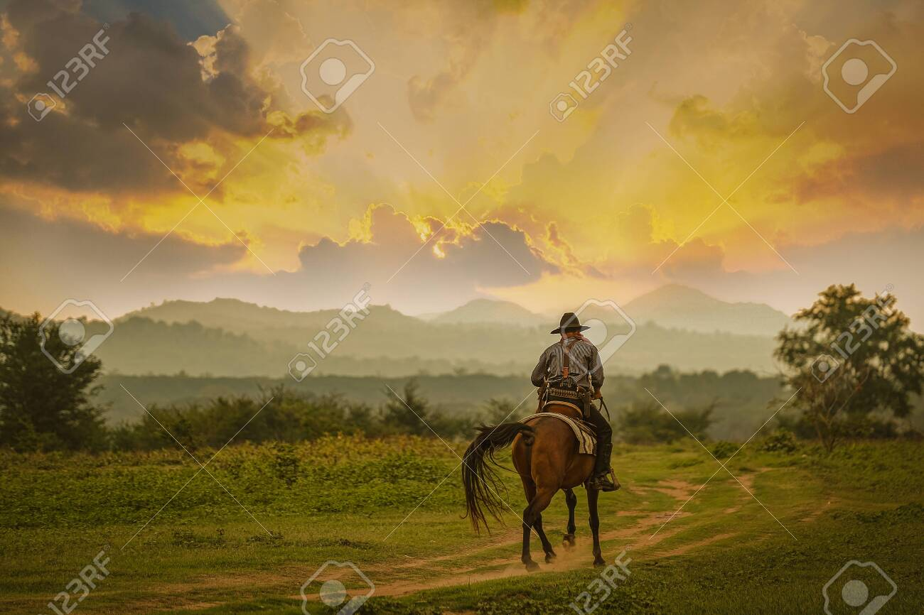 Silhouette Cowboy riding a horse under beautiful sunset - 130989357