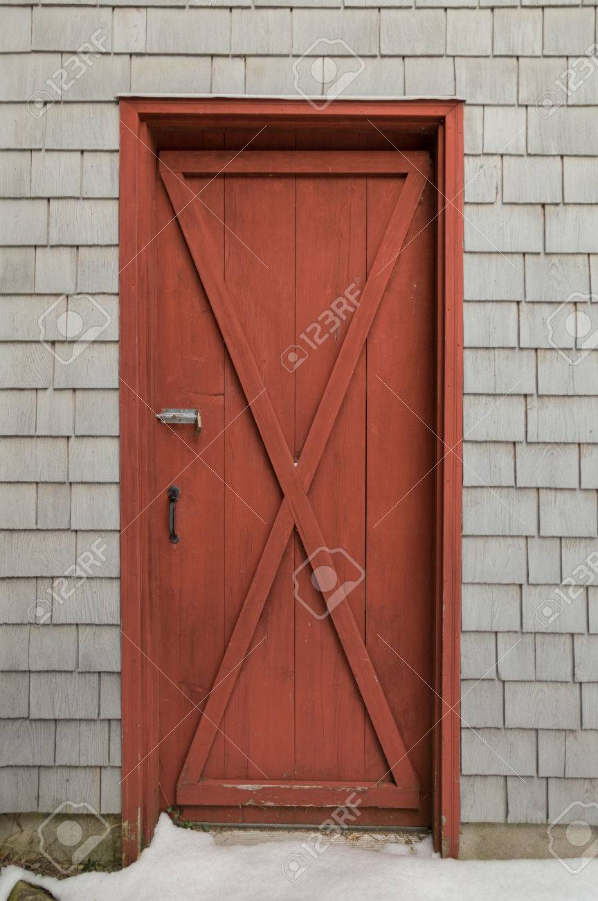 Oxblood red barn style X door on cedar shakes shingles background. Snow on the ground & Oxblood Red Barn Style X Door On Cedar Shakes Shingles Background ... pezcame.com
