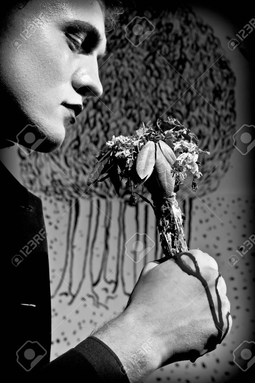 Un Jeune Homme Serre Son Poing Dans Un Bouquet De Fleurs Fanees