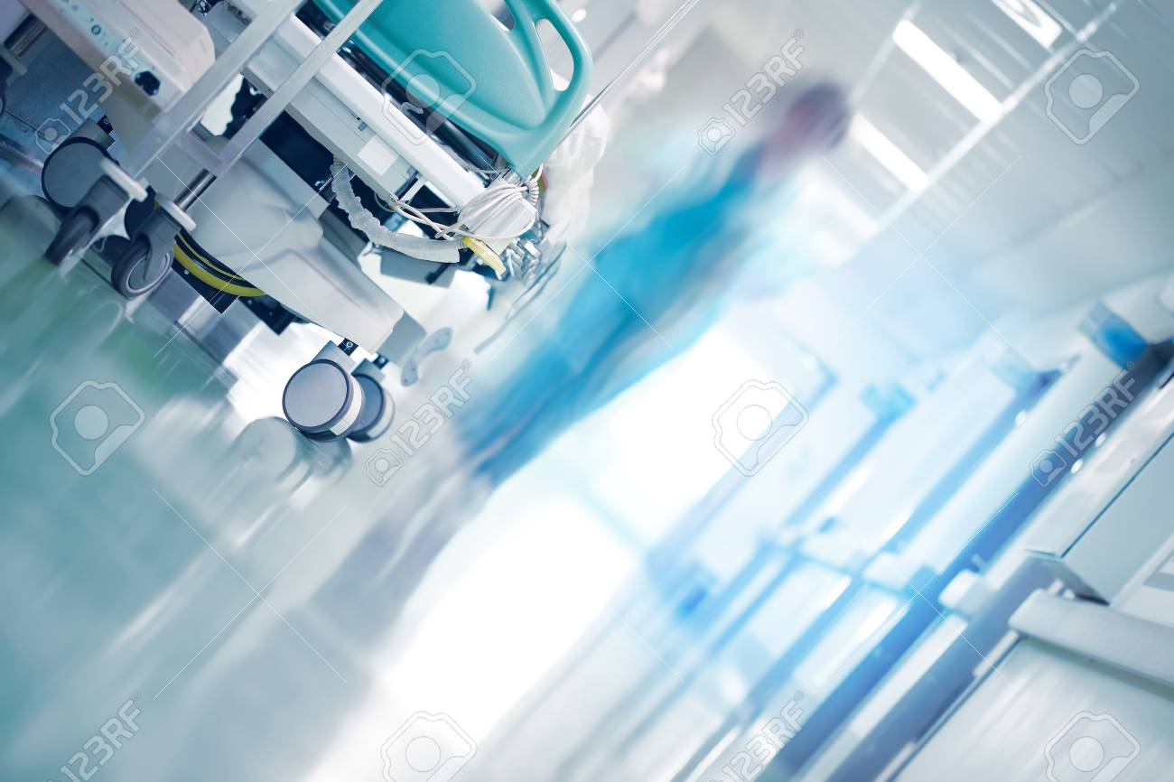 Medical bed in hospital hallway with professionals hurrying to the emergency case - 119762605