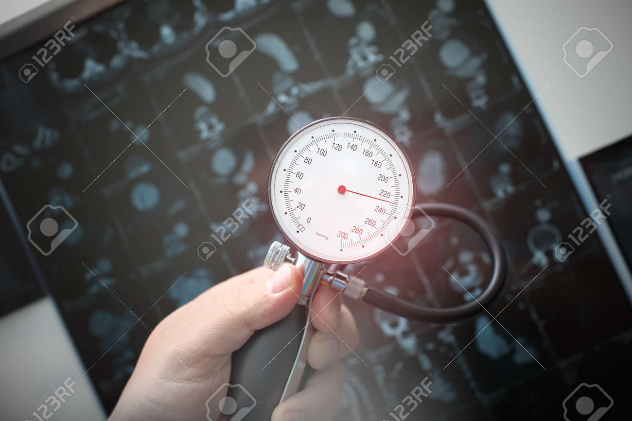 Pressure gauge in the hands of a doctor shows high blood pressure on the background of a CT scan. - 167523441