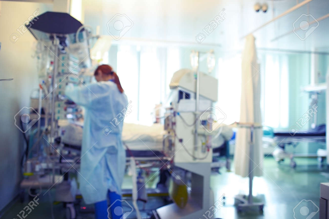 Ginger-haired female doctor working with patient in the ICU, unfocused background. - 166969562