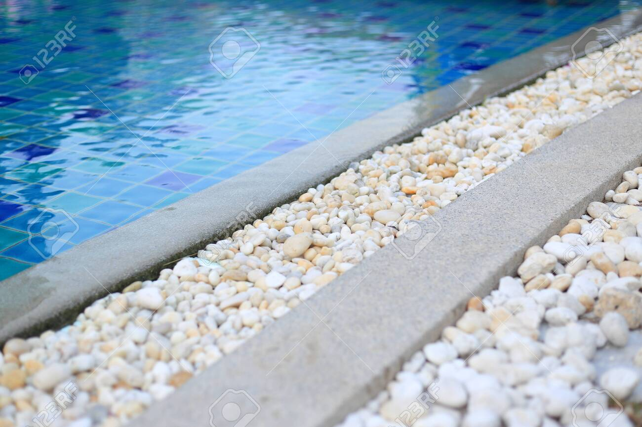 swimming pool grating covered with round white river pebble...
