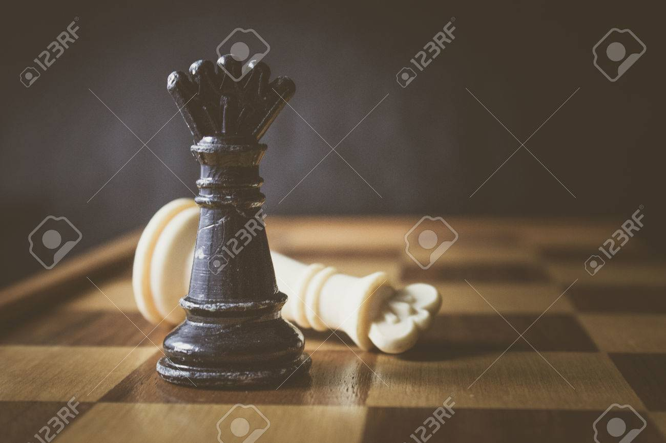 Fallen white king chess piece and black queen stock photo 65878242